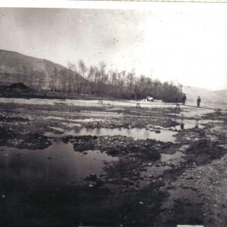 No hi havia cap pont per travessar el Besòs, sols es podia passar a peu per sobre d'uns taulons, el pont no es va inaugurar fins a la festa major d'estiu de 1915. AL fons es veu el turó de Montcada. .