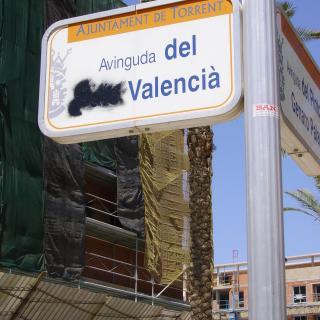 Senyal de l'avinguda del País Valencià corregida amb grafitti a Torrent, dies abans del canvi de nom  d'aquest carrer.