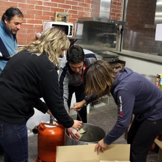 Voluntaris reparteixen caldo calent entre les persones evacuades per l'incendi al Baix Empordà, aquesta nit al pavelló de Sant Jordi Desvalls