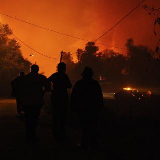 Uns veïns observen amb preocupació com les flames de l'incendi arriben als jardins de les cases