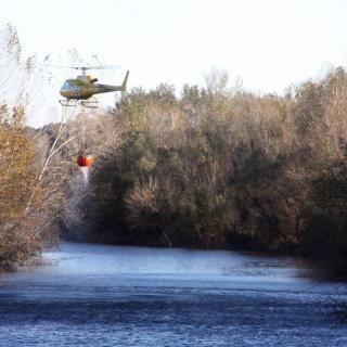 Un dels helicòpter que participa en les tasques d'extinció de l'incendi del Baix Empordà carrega aigua al riu Ter