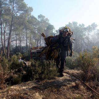 Un bomber carrega una mànega per pujar fins al cap del foc, a Foixà