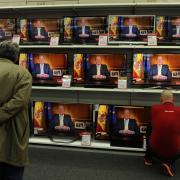 Un home observa el discurs d'abdicació del rei Joan Carles a les pantalles d'una botiga a Siero