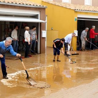 Gent treient aigua i fang de casa seva a  Vilamalla