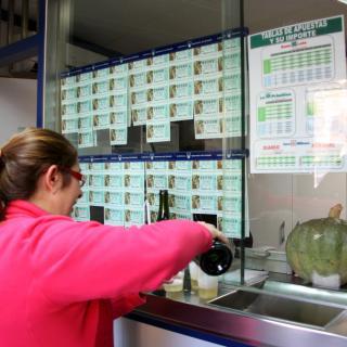 La venedora de l'administració de loteria número 1 de Santa Perpètua de Mogoda posant cava a l'interior de l'establiment