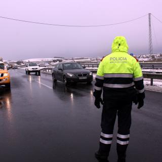 Un agent dels Mossos d'Esquadra controlant el trànsit a l'A-2 amb neu a la calçada, a l'alçada d'Anglesola