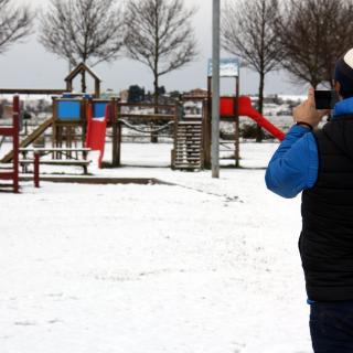Un home fent una foto amb el mòbil als seus fills que juguen amb la neu al parc de l'Ondara a Tàrrega