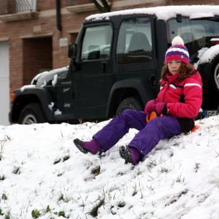 Una nena baixant de cul per la neu a Tàrrega