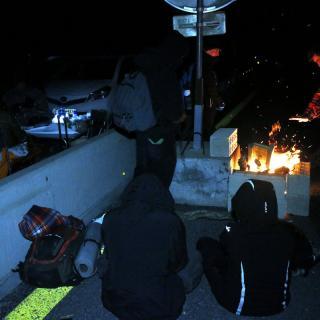 Acampats a l'AP-7 fan una foguera per escalfar-se
