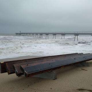 Els trossos de passera del Pont del Petroli que han arrencat les ones estan dispersats per tota la platja
