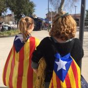 Una mare i la seva filla amb estelades a l'esquena camí de l'acte amb Puigdemont a Perpinyà
