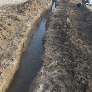 Els veïns obren una rasa (a pala) d'uns 80 metres a la platja per poder truere l'aigua del poble.