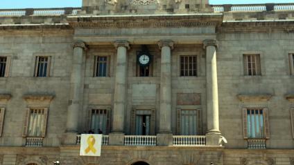 Operaris de l'Ajuntament pengen el llaç groc a la façana, aquest dilluns a Barcelona