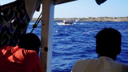 Alguns dels migrants rescatats per l''Open Arms', observant la costa de Lampedusa des del vaixell humanitari