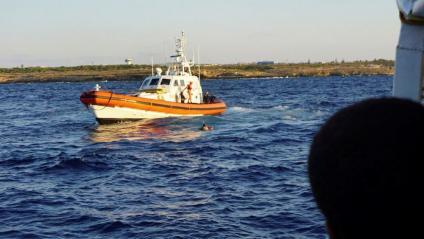 Una embarcació de la Guàrdia Costera italiana rescata un migrant que s'ha llançat a l'aigua des de l''Open Arms' per intentar arribar a l'illa de Lampedusa