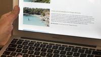 Una persona consulta una pàgina d'Internet, en un ordinador portàtil
