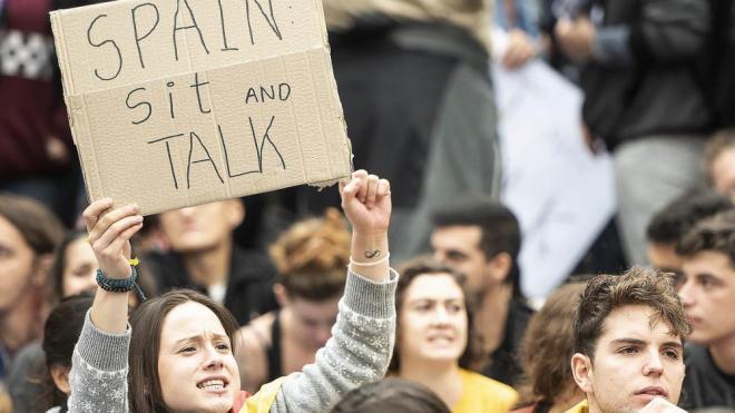 """Una manifestant mostra un cartell amb el lema """"Espanya, asseu-te i dialoga"""""""