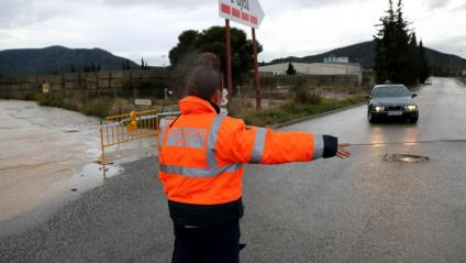 Una agent de protecció civil desvia el trànsit pels efectes de la pluja, aquest dimarts a Amposta