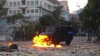 Un vehicle policial travessa un foc en un carrer ple d'objectes llançats pels manifestants, aquest diumenge a Hong Kong