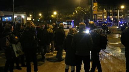 Un grup de persones s'estan a la vorera de l'avinguda Meridiana de Barcelona, aquest dijous després d'haver estat desallotjats pels Mossos d'Esquadra del mig de la via