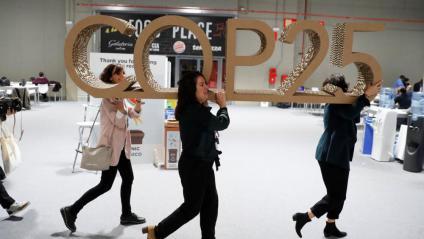 Tres dones retiren un logotip de la cimera COP25, aquest diumenge a Madrid