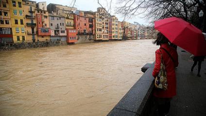Una dona observa el riu Onyar al seu pas per Girona, aquest dimarts