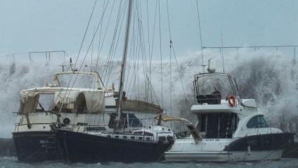 Les onades han superat el mur de l'escullera del Port Olímpic de Barcelona i l'aigua ha enfonsat un vaixell
