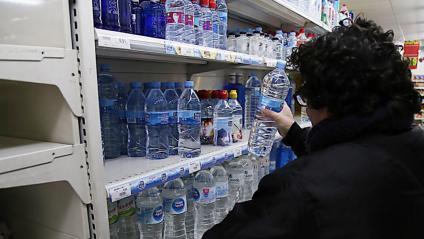 Un veí de Girona compra aigua envasada en un supermercat, arran de les restriccions que s'han imposat aquest dijous a l'aigua d'aixeta