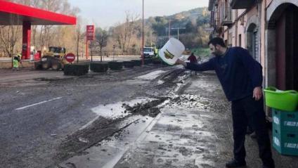 Un home buida aigua d'un local afectat pel desbordament del riu, aquest divendres a Girona