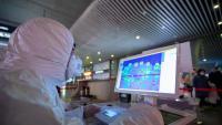 Un treballador sanitari monitoritza la temperatura dels usuaris de l'estació de tren de Nanjing, a la xina