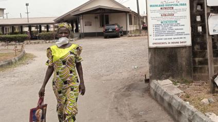 Una dona amb una màscara passa davant l'hospital de Yuba, a Lagos, on és ingressat el primer pacient diagnosticat amb el Covid-19 a Nigèria