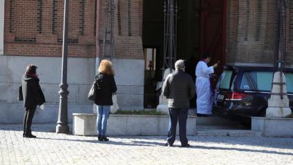 Un sacerdot oficia unes exèquies al cementiri de l'Almudena de Madrid. Les comitives funeràries s'han limitat a tres familiars o persones properes al difunt, a més de l'oficiant