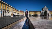 Una dona camina per la plaça del Comércio de Lisboa, gairebé buida pel confinament de la població