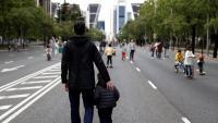 Un home passeja amb un nen, al passeig de la Castellana de Madrid