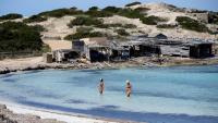Dues persones es banyen a la platja de Ses Illetes, a Formentera, un dels territoris on la desescalada està més avançada