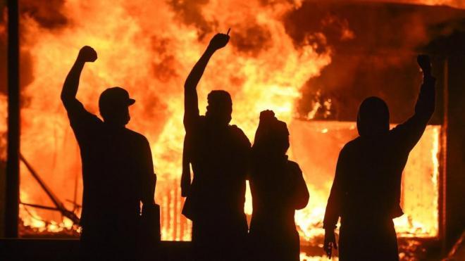 Un grup de persones alça el puny davant un establiment en flames durant els aldarulls per la mort de George Floyd, aquest divendres a la nit a Minneapolis