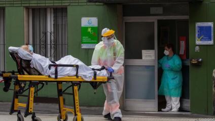 Un sanitari trasllada a l'hospital un dels resident de la residència El Carmen de Gijón, que s'han infectat de Covid-19