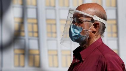 Un home passeja amb mascareta i pantalla protectora, a Madrid