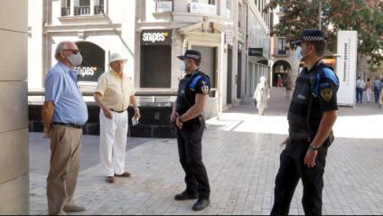 Dos agents de la Guàrdia Urbana recorden a un home la necessitat de dur mascareta, diumenge passat a l'Eix Comercial de Lleida