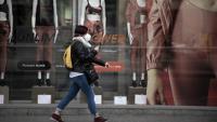 Una persona passa davant l'aparador d'una botiga de roba, al carrer Pelai de Barcelona