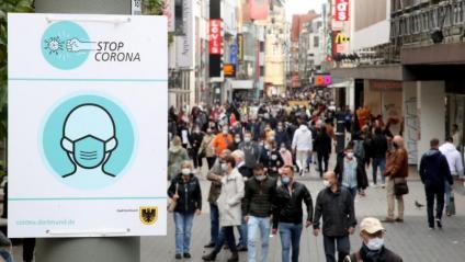 Un cartell insta a portar la mascareta, en un carrer comercial de Dortmund, a Alemanya