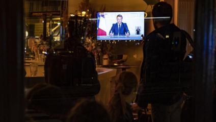 Els clients d'un cafè escolten el discurs del president francès, Emmanuel Macron, aquest dimecres a París