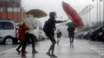 Diverses persones es protegeixen del temporal que afecta la costa mediterrània, aquest divendres a València