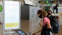 Una passatgera es desinfecta les mans a l'entrada de la terminal, a l'aeroport de Barcelona-El Prat
