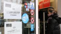 Dos cartells recorden les mesures per la Covid-19, a l'entrada d'una botiga
