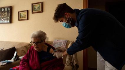 Un infermer del CAP de La Marina administra la primera dosi de la vacuna de Pfizer a una dona major de 80 anys al seu domicili, a Barcelona