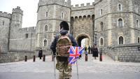Una persona amb una bandera del Regne Unit, aquest dissabte davant el castell de Windsor