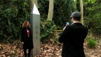 Una noia es fa una foto al costat del monòlit, a l'arbreda de Santes Creus