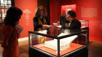 Visitants de l'exposició observen un dels exemplars exhibits, a la Biblioteca Nacional d'Espanya