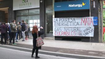 Una dona captura una imatge de la seu de Gas Natural a Reus, on els manifestants han enganxessin dues pancartes